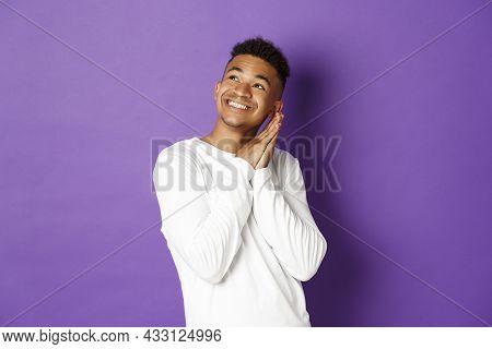 Image Of Happy African-american Man In White Sweatshirt, Feeling Pleased, Looking Dreamy At Upper Le