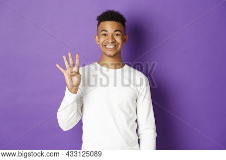 Image Of Cheerful African-american Guy In White Sweatshirt, Showing Number Four And Smiling, Standin