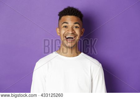 Close-up Of Joyful African-american Man In White Sweatshirt, Laughing And Looking Amazed At Camera,