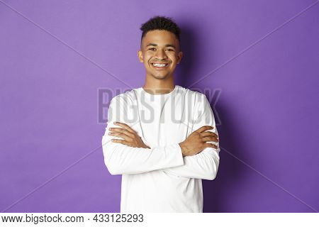 Portrait Of Handsome African-american Male Student In White Sweatshirt, Cross Arms On Chest And Smil