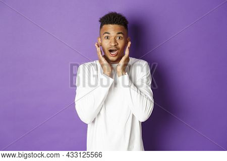 Portrait Of Handsome African-american Male Model In White Sweatshirt, Looking Amazed And Impressed,