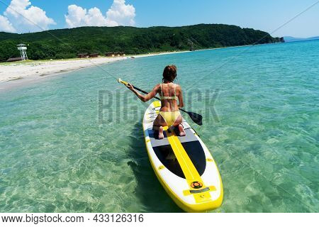 Back View Sportswoman In Swimsuit Floating On Sup With Paddle Enjoying Recreational Activity