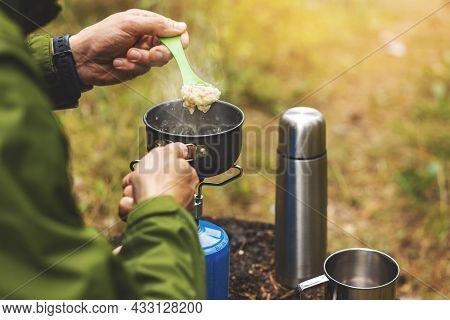 Preparing Oatmeal Porridge Outdoors On Gas Burner. Camping Cooking Equipment