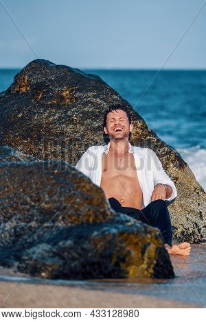 Delighted Trendy Male In Wet Apparel Sitting Near Rock On Beach And Laughing While Enjoying Summer