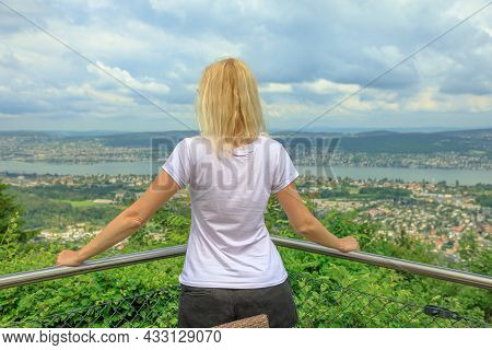 Backside Of Woman Looking Zurich City Lake And Skyline From Top Of Felsenegg Cable Car. Blonde Touri