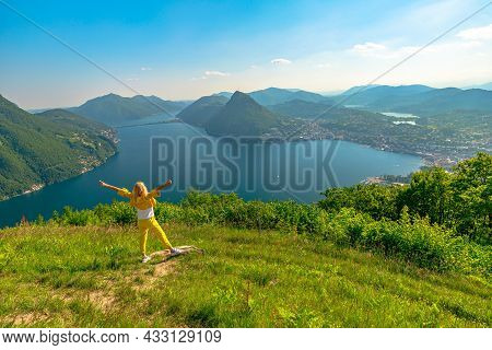 Swiss Woman With Open Arms On Top Of Lugano Corniche By Lugano Lake In Switzerland. Aerial View Look