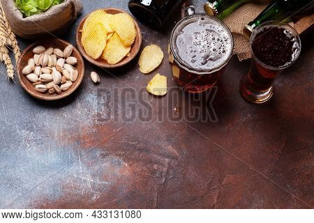 Lager beer mug, bottles, hops and wheat on old stone table. Top view with copy space