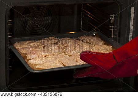 Cooking Chicken Meat In The Oven. A Baking Sheet With Raw Chicken Pieces Is Placed In The Electric O