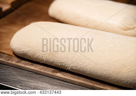 A Piece Of Raw French Bun Dough Against The Background Of Other Bun Dough Pieces. Raw Craft Bread Do