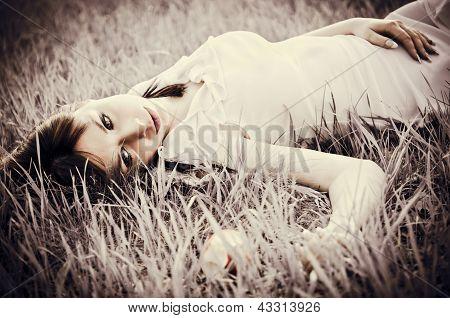 Sad Beautiful Girl Lying On Grass. Faded Effect