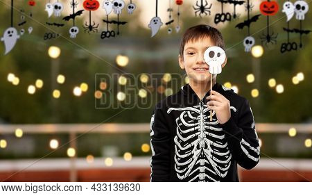 halloween, holiday and childhood concept - smiling boy in black costume of skeleton with scull party prop over roof top background
