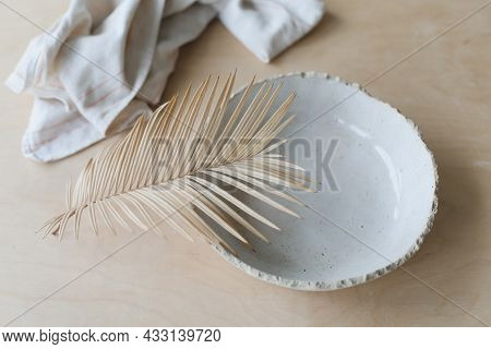 Ceramic Plate On A Wooden Table Top View. Minimalist Handmade Ceramic Tableware And Pottery