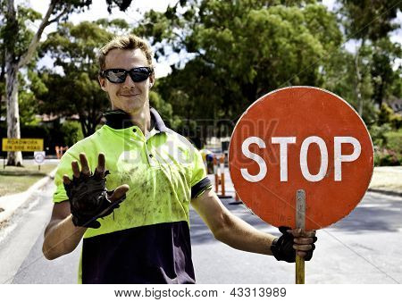 Road worker controls traffic flow using stop sign poster
