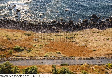 Magnificent Aerial View Of The Seaside With A Dark Strip Of Rocky Beach And Bright Orange Field Plan