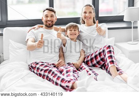 family, rest and people concept - happy mother, father and little son in matching pajamas showing thumbs up in bed in morning