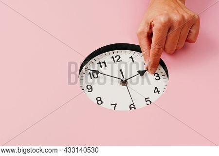 the hand of a young caucasian man sets a clock backward or forward, at the end or at the beginning of the summer, on a pink background