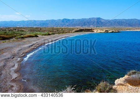 a view over the lonely El Saladar beach, in Aguilas, in the Costa Calida coast, Region of Murcia, Spain, with the Calnegre mountain range in the background