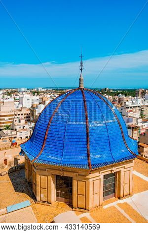 the blue tiled dome of the Basilica of Santa Maria church in Elche, Spain, and an aerial view of the old town of the city