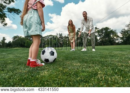 Closeup Of Little Girl Ready For Kicking The Ball. Young Family Playing Football On The Grass Field