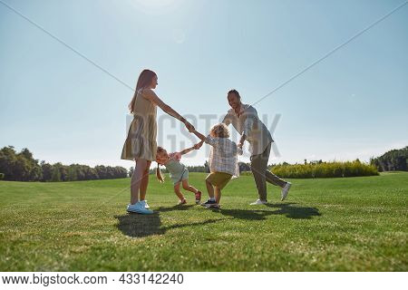 Active Young Parents Spending Time Together, Holding Hands In Circle With Their Two Little Kids, Boy