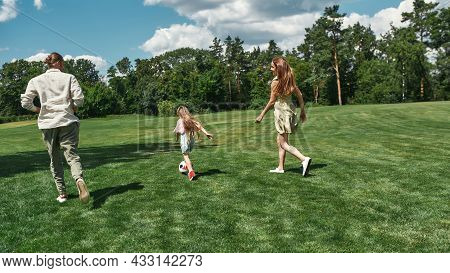 Active Young Family Playing Football Together With Little Daughter On The Grass Field In The Park On