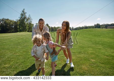 Active Parents With Two Little Kids Playing Catch Together In Green Park On A Summer Day. Happy Fami