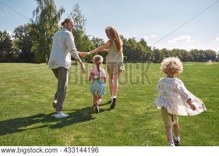 Happy Parents Holding Hands, Playing On Grass Field With Their Little Kids, Boy And Girl, Having Fun