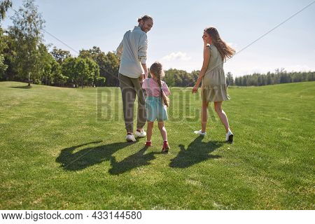 Active Little Girl Having Fun Together With Her Parents, Catching Them In Green Park On A Summer Day