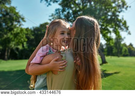 Loving Mother Cuddling With Her Cute Little Daughter, Holding Her While Relaxing Together In Summer