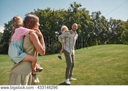 Little Kids Enjoying Piggyback Ride On The Back Of Their Mom And Dad. Family Walking In Green Summer