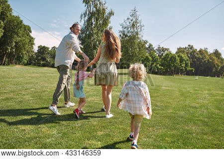 Back View Of Young Parents Running, Playing On Grass Field With Their Little Kids, Boy And Girl On A