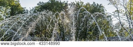 Splashing Water In The Fountain At Summer City Public Urban Park. Water Jets Abstract Image Close-up