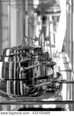 stainless steel pots on glass shelf
