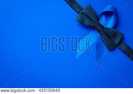 November. Blue Ribbon, Fashion Bowtie Isolated On Deep Blue Background. Awareness Prostate Cancer Of