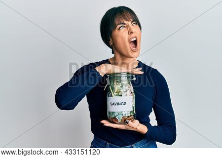 Young hispanic woman holding savings jar angry and mad screaming frustrated and furious, shouting with anger. rage and aggressive concept.