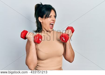 Young hispanic woman wearing sportswear using dumbbells angry and mad screaming frustrated and furious, shouting with anger. rage and aggressive concept.