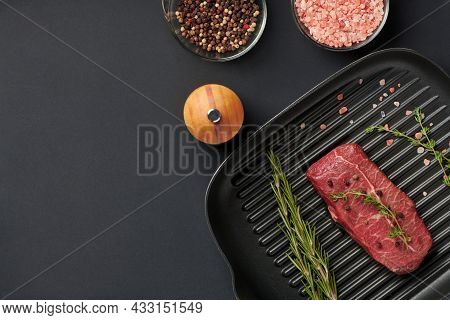 Raw Fresh Beef Top Blade Steak On Grill Pan With Rosemary And Thyme Ready For Cooking. Marbled Meat