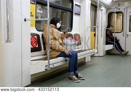 Moscow, Russia - September 2021: People In A Metro Train, Girl In Mask Sits With Smartphone And Bouq