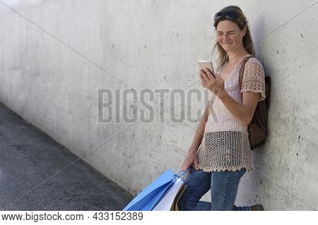 Woman With Shopping Bags Using Cell Phone Leaning Against Gray Wall