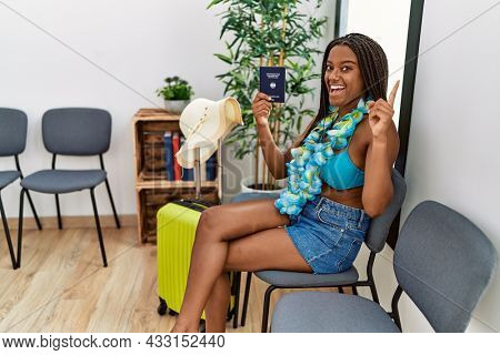 Young african american woman holding deutschland passport going on vacation smiling happy pointing with hand and finger to the side