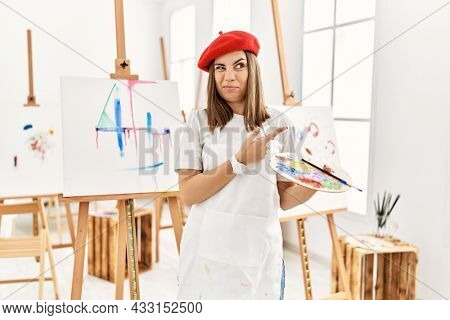 Young artist woman painting on a canvas at art studio pointing aside worried and nervous with forefinger, concerned and surprised expression