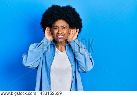 Young african american woman wearing casual clothes trying to hear both hands on ear gesture, curious for gossip. hearing problem, deaf