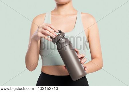 Active woman holding a stainless steel water bottle