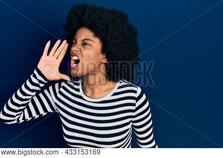 Young african american woman wearing casual clothes shouting and screaming loud to side with hand on mouth. communication concept.