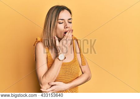 Young caucasian blonde woman wearing casual yellow t shirt bored yawning tired covering mouth with hand. restless and sleepiness.