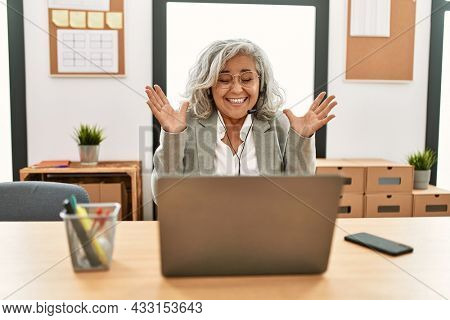 Middle age businesswoman sitting on desk working using laptop at office celebrating mad and crazy for success with arms raised and closed eyes screaming excited. winner concept