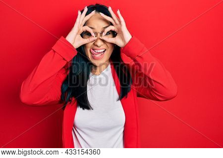 Beautiful hispanic woman with nose piercing wearing casual look and glasses doing ok gesture like binoculars sticking tongue out, eyes looking through fingers. crazy expression.