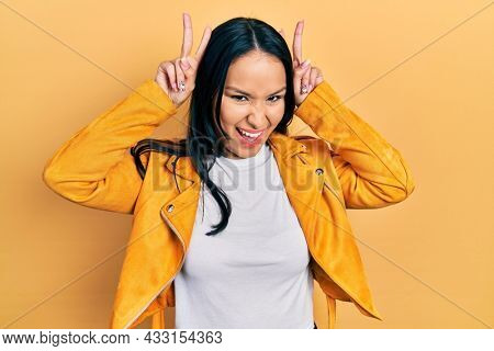 Beautiful hispanic woman with nose piercing wearing yellow leather jacket posing funny and crazy with fingers on head as bunny ears, smiling cheerful