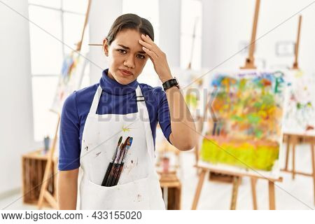 Young brunette woman at art studio worried and stressed about a problem with hand on forehead, nervous and anxious for crisis
