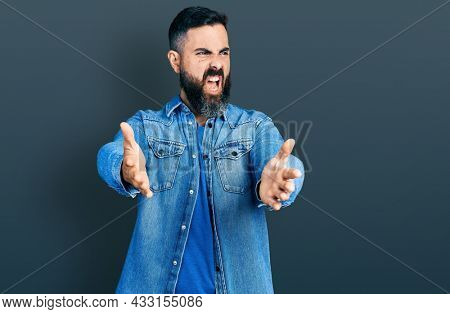 Hispanic man with beard with open arms doing hug gesture angry and mad screaming frustrated and furious, shouting with anger. rage and aggressive concept.